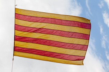Flag Catalonia above blue cloudy sky