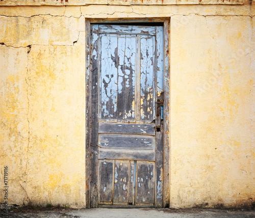 Old wooden door in yellow wall. Background photo texture - 71719116