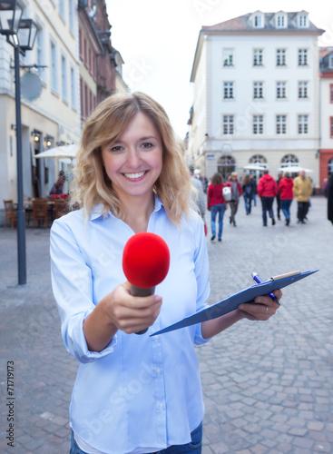 canvas print picture Frau mit blonden Locken interviewt einen Passanten