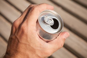 Aluminum can of beer in a male hand, summer outdoor photo