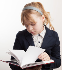 Close-up portrait of blond Caucasian schoolgirl reading textbook
