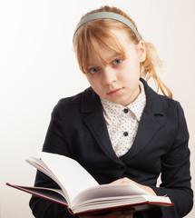 Closeup portrait of blond Caucasian schoolgirl with book