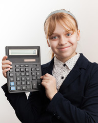 Little blond smiling schoolgirl with calculator above white
