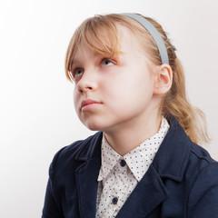 Closeup portrait of blond Caucasian thinking schoolgirl  on whit