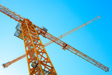 Modern yellow industrial cranes above bright blue sky