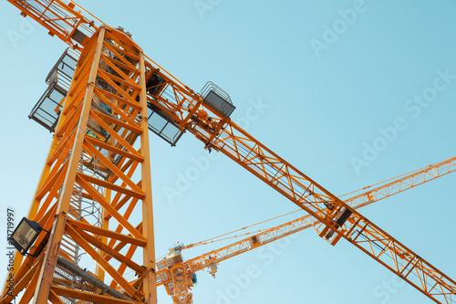 Modern yellow construction cranes above blue sky - 71719997