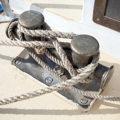 Dark bollard with rope knot on yacht deck