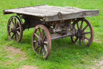 Empty old rural wooden wagon stands on green summer grass