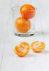 Juicy tangerines in glass on a white wooden surface