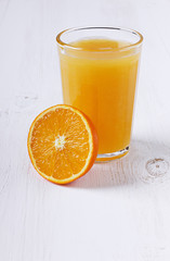 Fresh juice in a glass with an orange half
