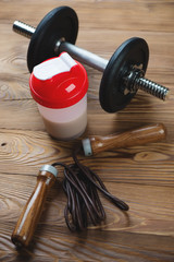 Protein shake with sports equipment over wooden background