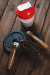 Jumping rope, weight disks and a protein shake, vertical shot