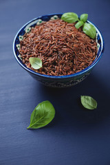 Red kernel rice in a ceramic pialat, vertical shot, close-up