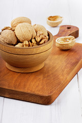 Walnuts in a wooden bowl on a brown board