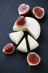 Sliced cheese and fig fruits over black wooden surface