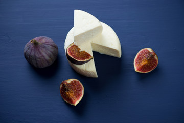 Sliced cheese and fig fruits on a dark blue wooden background