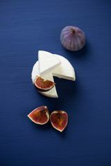 Cheese and figs over dark blue wooden surface, view from above