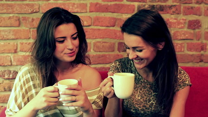 Female friends drinking coffee and smiling to the camera