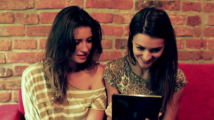 Female friends using tablet and smiling to the camera