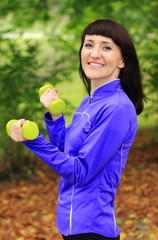 Brunette during fitness exercise with dumbbells in autumn park