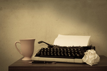 Typewriter with coffee cup and pen,sepia color filtered.