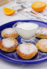 Fritters of cottage cheese with sour cream on a white background