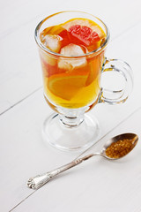 Glass of ice tea with citrus on a light background