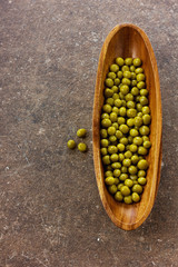 Canned green peas in wooden bowl