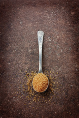 Brown sugar in a spoon on a vintage surface
