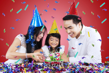 Asian family cutting a birthday cake