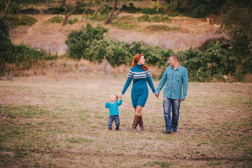 Happy family in blue stylish clothes walking in autumn forest