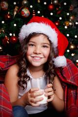 Sweet little girl drinking a glass of milk before sleeping