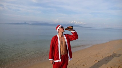 Santa Claus Drinking Beer on Beach Celebrating Christmas. Slow
