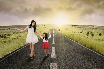 Cheerful girl and her mother on road