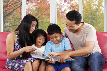 Children read a story book with parents