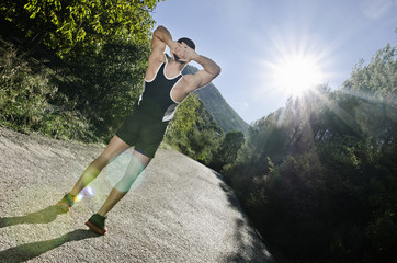 Runner warming arms and back with sun flare