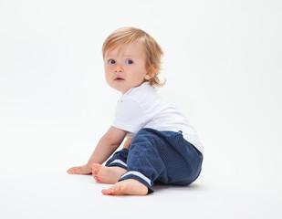 Kleiner Blonder Junge sitzt und schaut