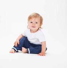Kleiner süßer blonder Junge sitzt und lacht