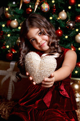 Beautiful young girl showing a heart