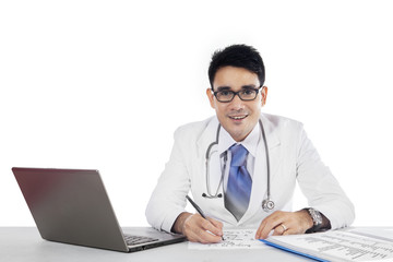 Doctor writes a prescription and looking at camera