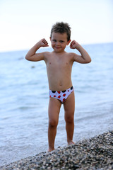 boy on the beach shows how strong he is