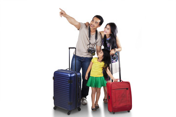 Family with luggage looking copyspace