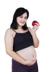 Healthy pregnant woman holding apple