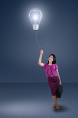 Hispanic businesswoman and lightbulb