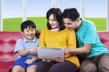 Little boy and his family using tablet