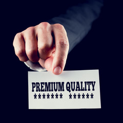 Businessman holding a card saying Premium Quality