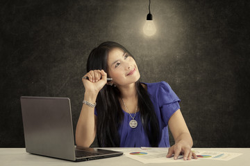 Smiling businesswoman and bright lamp