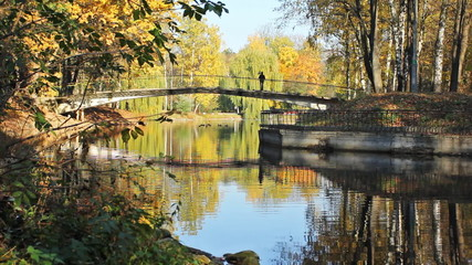 bridge across lake in beautiful autumn city park
