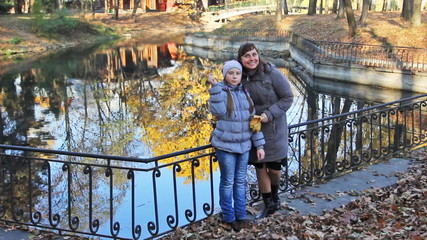 mother and daughter with yellow leaves in their hands near lake