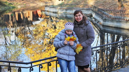 mother and daughter with yellow leaves stand huging near lake